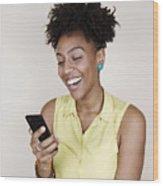 Woman smiling using phone Wood Print