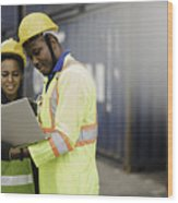 Young African american men and woman worker Check and control loading freight Containers by use computer laptop at commercial shipping dock felling happy. Cargo freight ship import export concept Wood Print