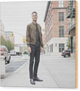 Young man standing on city sidewalk Wood Print
