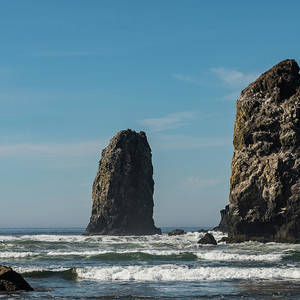 The Waves Crashing On Vertical Rocks Protruding In Cannon Beach